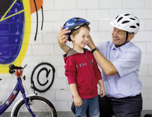 Mann setzt kleinem Jungen einen Fahrradhelm auf