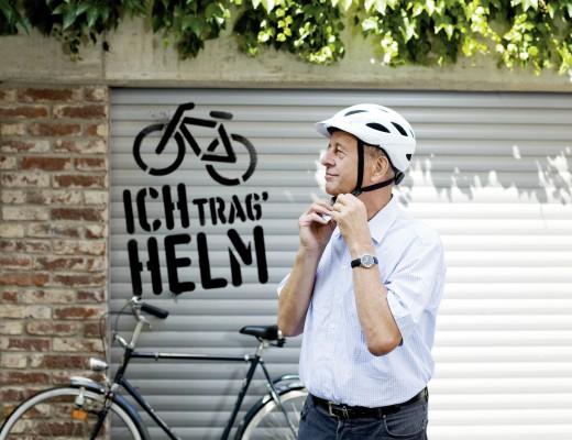 Ich trag' Helm Mann zieht Fahrradhelm auf