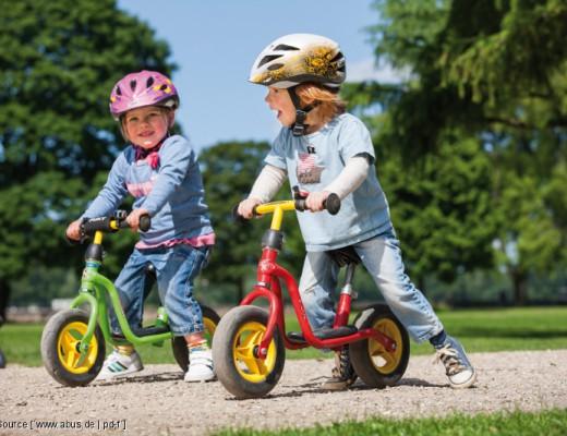 Junge und Mädchen auf Laufrädern mit Fahrradhelm