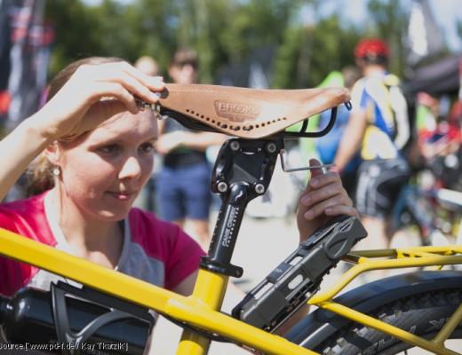 Frau stellt Sitzposition des Fahrradsattels ein